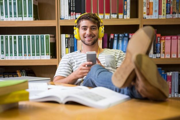 Estudante escuta música na biblioteca com smartphone