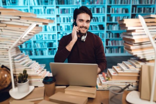 Estudante está usando o laptop e falando no telefone.