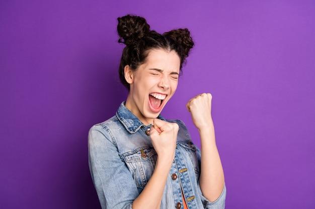 Estudante estilosa com cabelo encaracolado posando contra a parede roxa
