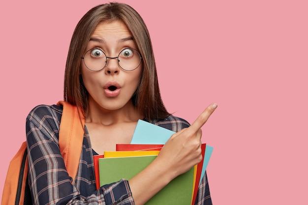 Estudante estupefato posando contra a parede rosa com óculos