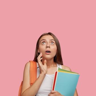 Estudante estupefato posando contra a parede rosa