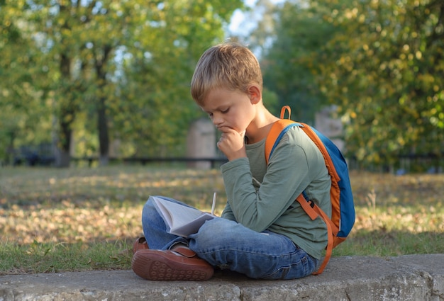 Estudante europeu fazendo lição de casa em um caderno, sentado em um lindo parque de outono