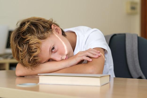 Estudante exausto deitado na mesa da sala de aula