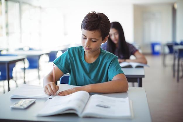 Estudante fazendo lição de casa em sala de aula