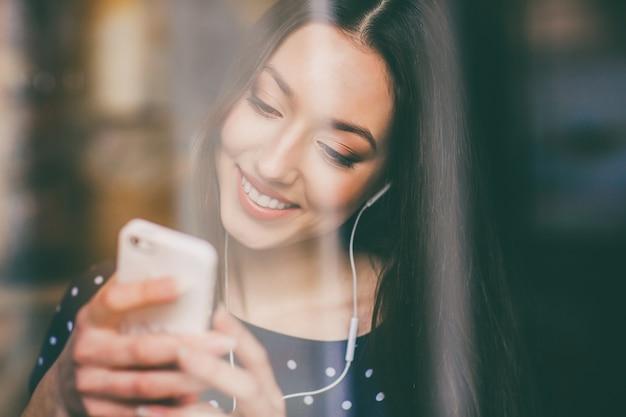 Estudante feliz brincando com seu celular