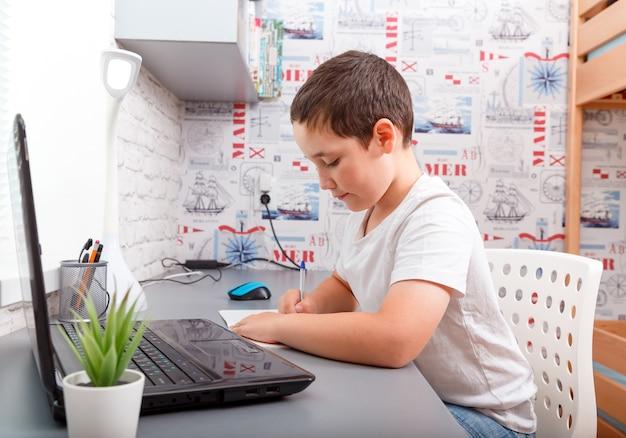 Estudante feliz, caucasiano, fazendo lição de casa sentado na mesa.
