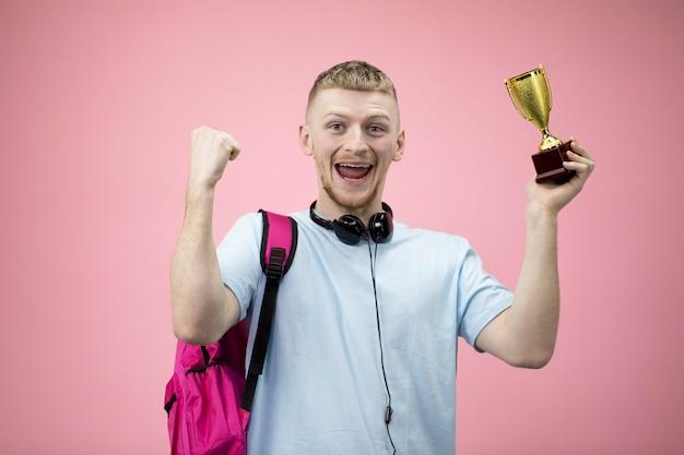 Estudante feliz comemora sua vitória com as mãos para cima e mantém o copo na mão