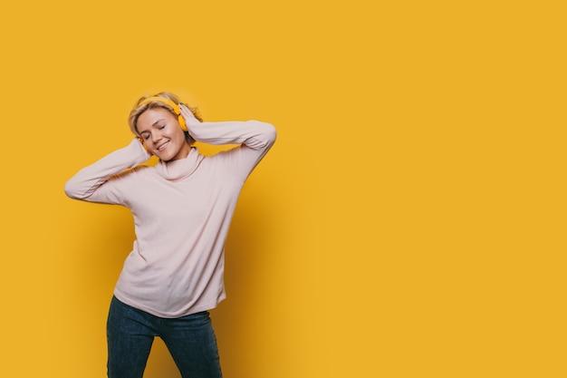 Estudante feliz e alegre ouvindo música perto de um espaço amarelo em branco