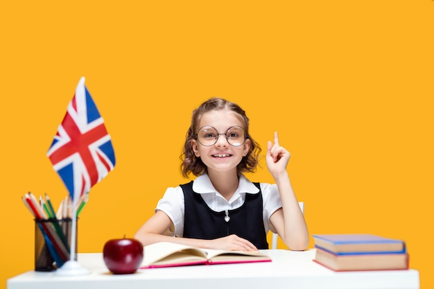 Estudante feliz e sorridente, caucasiana, levantando o dedo indicador, aula de inglês, bandeira da grã-bretanha