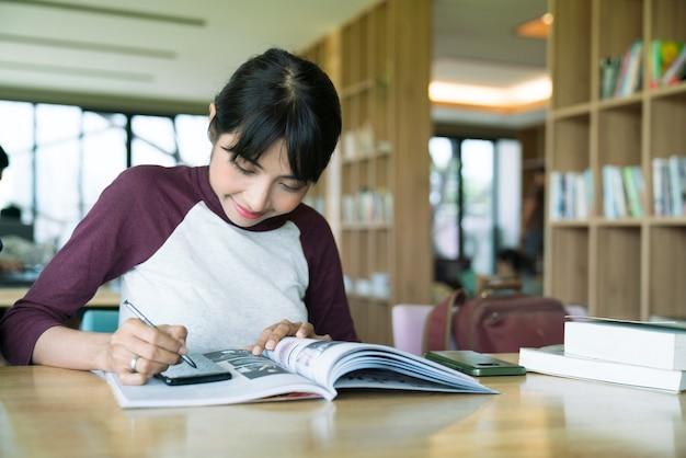 Estudante feliz, estudando e aprendendo a tomar notas com um tablet digital