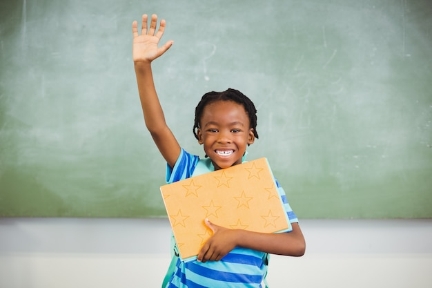 Estudante feliz, levantando a mão e segurando livros na sala de aula