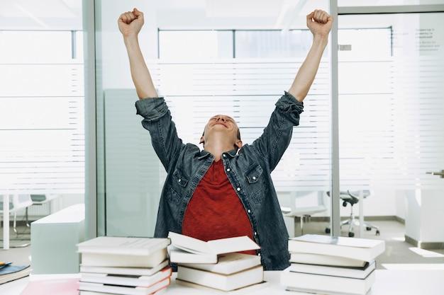 Estudante feliz mostra thumbs up trabalhando com livros na biblioteca