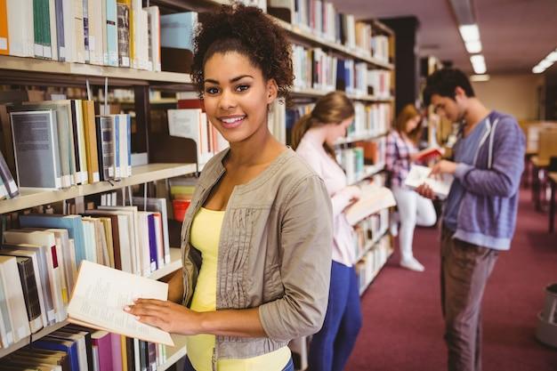 Estudante feliz pegando livro da prateleira