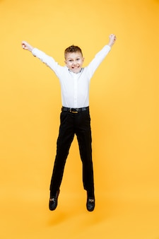 Estudante feliz pulando de alegria. isolado sobre a superfície amarela. felicidade, atividade e conceito de criança.