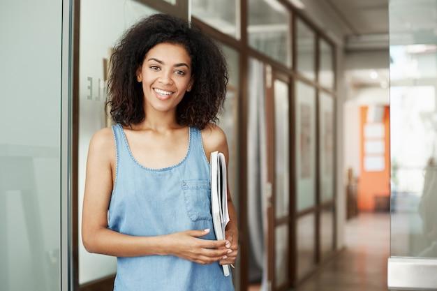 Estudante fêmea africana bonita nova que sorri guardando livros na faculdade.