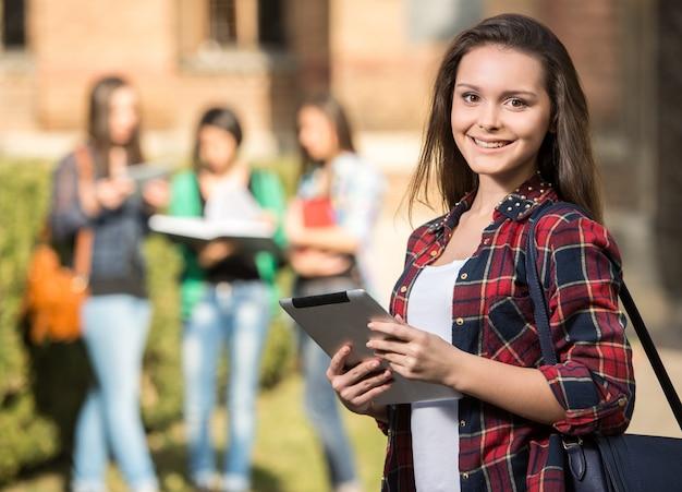 Estudante fêmea bonita nova na faculdade, ao ar livre.