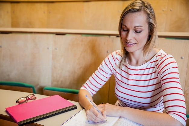 Estudante fêmea feliz que escreve notas na universidade