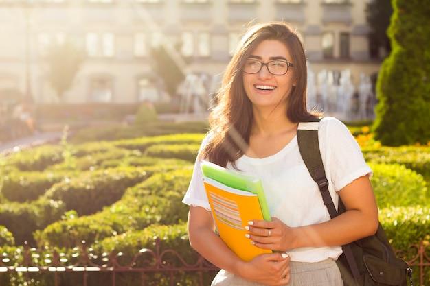 Estudante fêmea novo feliz com os livros nas mãos no fundo da universidade.