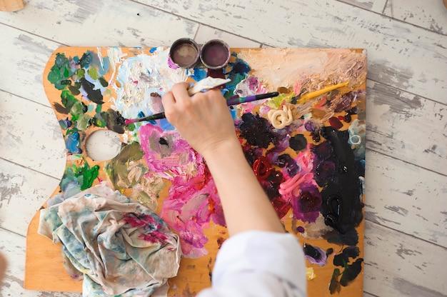 Estudante fêmea novo que tem classes no estúdio da arte, tentando misturar aquarelas diferentes no cartão.
