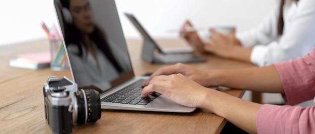 Estudante feminino feminino digitando no laptop enquanto está sentado na mesa de trabalho com a amiga na biblioteca
