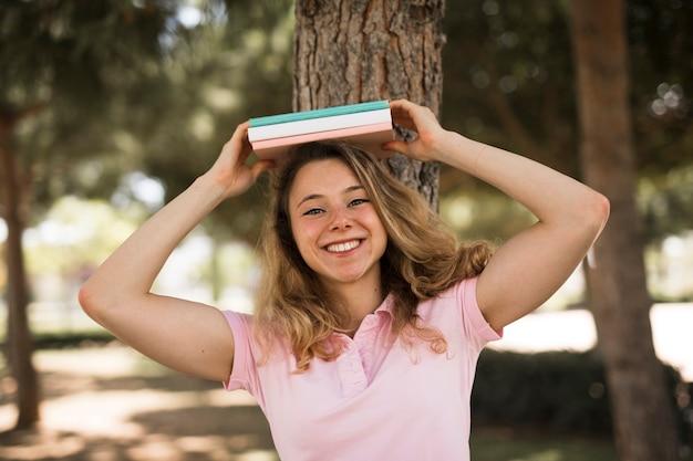 Estudante feminino segurando livros acima da cabeça