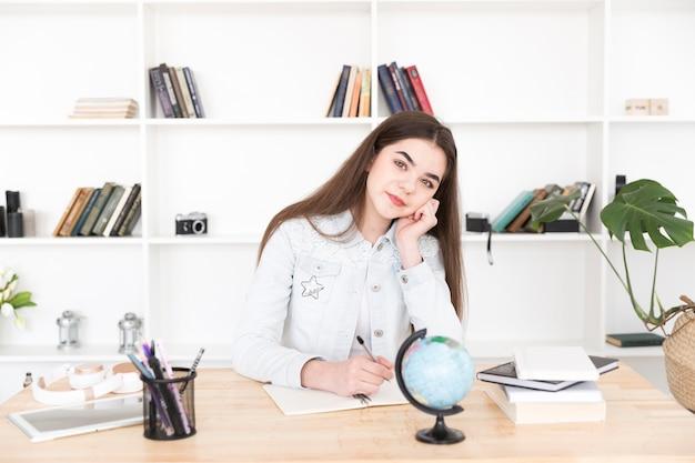 Estudante feminino, sentando, caneta segurando, e, pensando