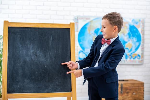 Estudante fica perto do quadro-negro na sala de aula e aponta para ele com os dedos