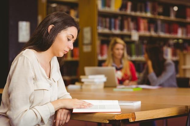 Estudante focado sentado na mesa lendo livro de texto