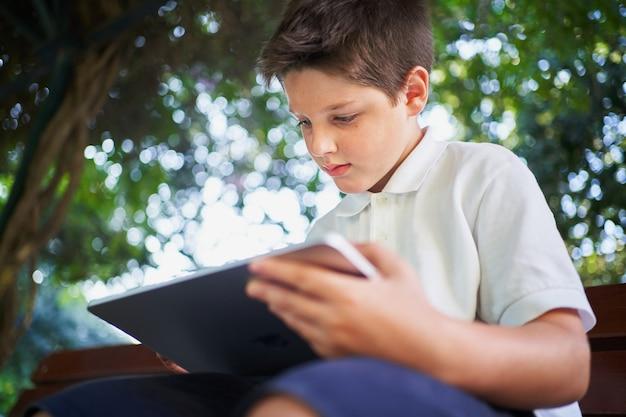 Estudante focado usando tablet com lápis digital em uma árvore