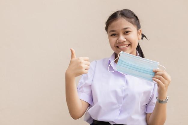 Estudante fofo asiático em uniforme feliz com máscara facial polegares para cima para uma boa saúde.