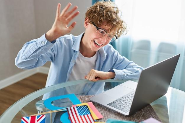 Estudante fofo dizendo olá para a câmera enquanto dá aula online em casa