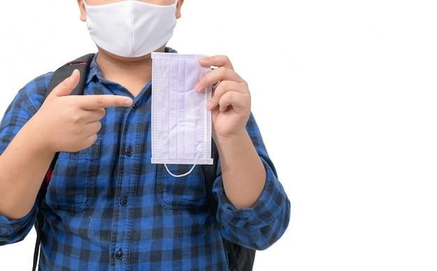 Estudante gordo usa máscara e aponta o dedo para uma máscara cirúrgica