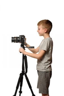 Estudante grava vídeo na câmera dslr. vista lateral. fundo branco, isolar