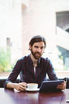 Estudante hipster usando tablet na cantina