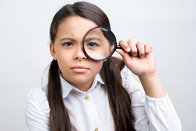 Estudante hispânica atenta, olhando através de lupa