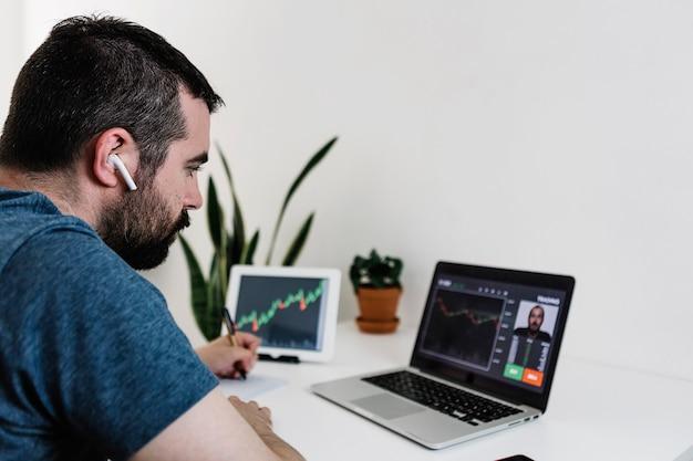 Estudante hispânico fazendo uma videochamada com um trader profissional para aprender a negociar