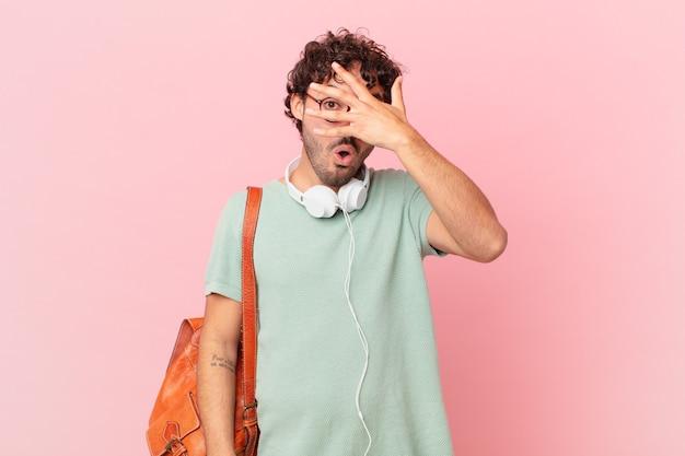 Estudante hispânico parecendo chocado, assustado ou apavorado, cobrindo o rosto com a mão e espiando por entre os dedos