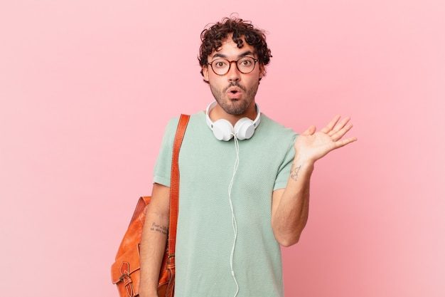 Estudante hispânico parecendo surpreso e chocado, com o queixo caído segurando um objeto com a mão aberta na lateral
