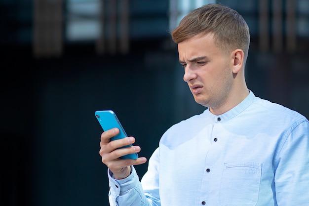 Estudante imprime mensagem, homem descontente em seu smartphone móvel. homem bravo jovem empresário