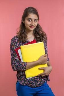 Estudante indiano bonito com livros e pastas nas mãos. jovem professora.