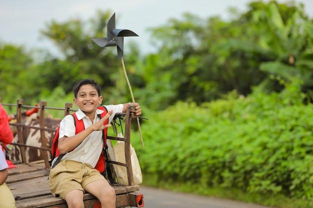 Estudante indiano fofo em um carro de boi