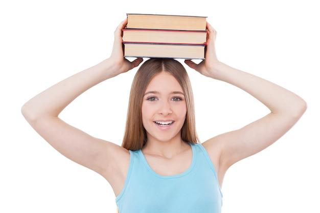 Estudante inteligente. adolescente alegre segurando uma pilha de livros na cabeça e sorrindo enquanto fica de pé, isolado no branco