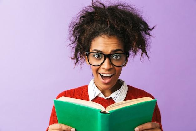 Estudante inteligente afro-americano em uniforme segurando e lendo livro, isolado