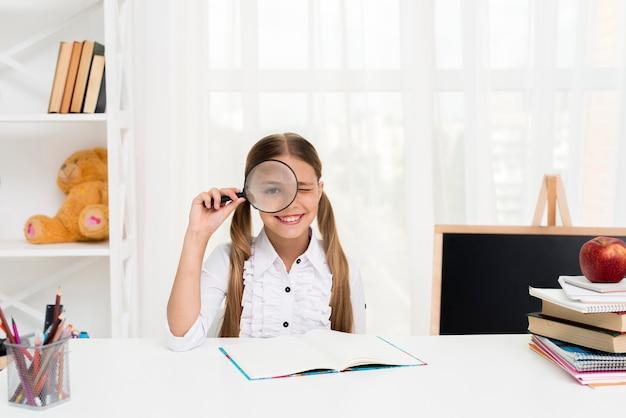 Estudante inteligente, olhando através de lupa