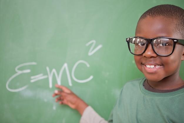 Estudante inteligente que mostra a equivalência em massa de energia