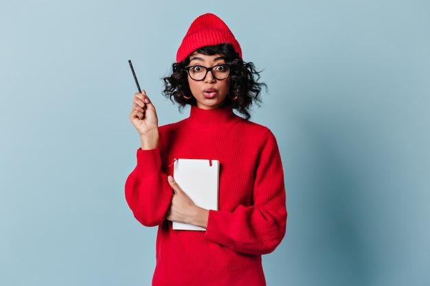 Estudante internacional chocado segurando caneta e caderno