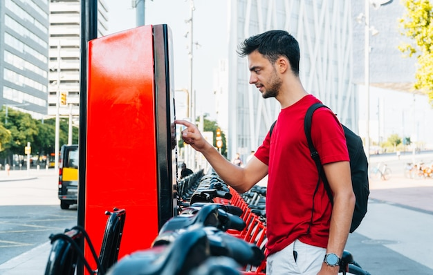 Estudante jovem adulto alugando bicicleta em cidade grande