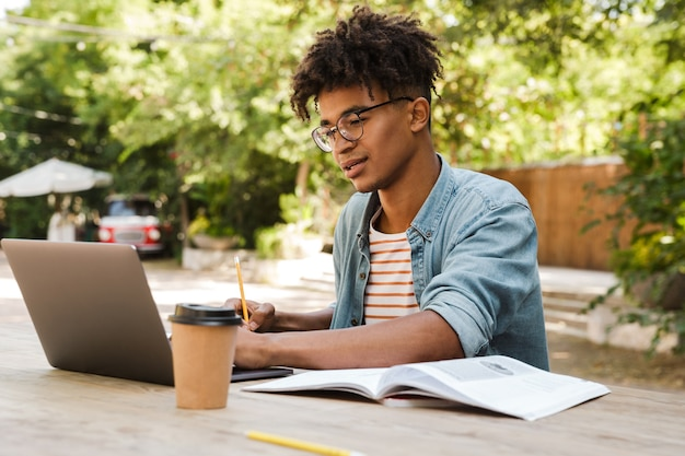 Estudante jovem africano confiante estudando no parque