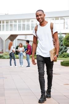 Estudante jovem afro-americano feliz com mochila caminhando ao ar livre
