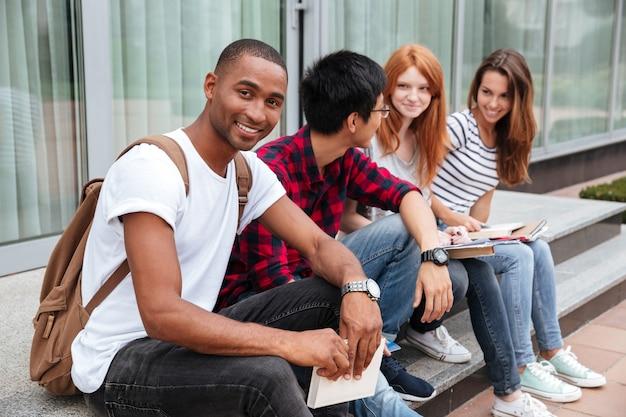 Estudante jovem afro-americano feliz sentado com seus fritos ao ar livre